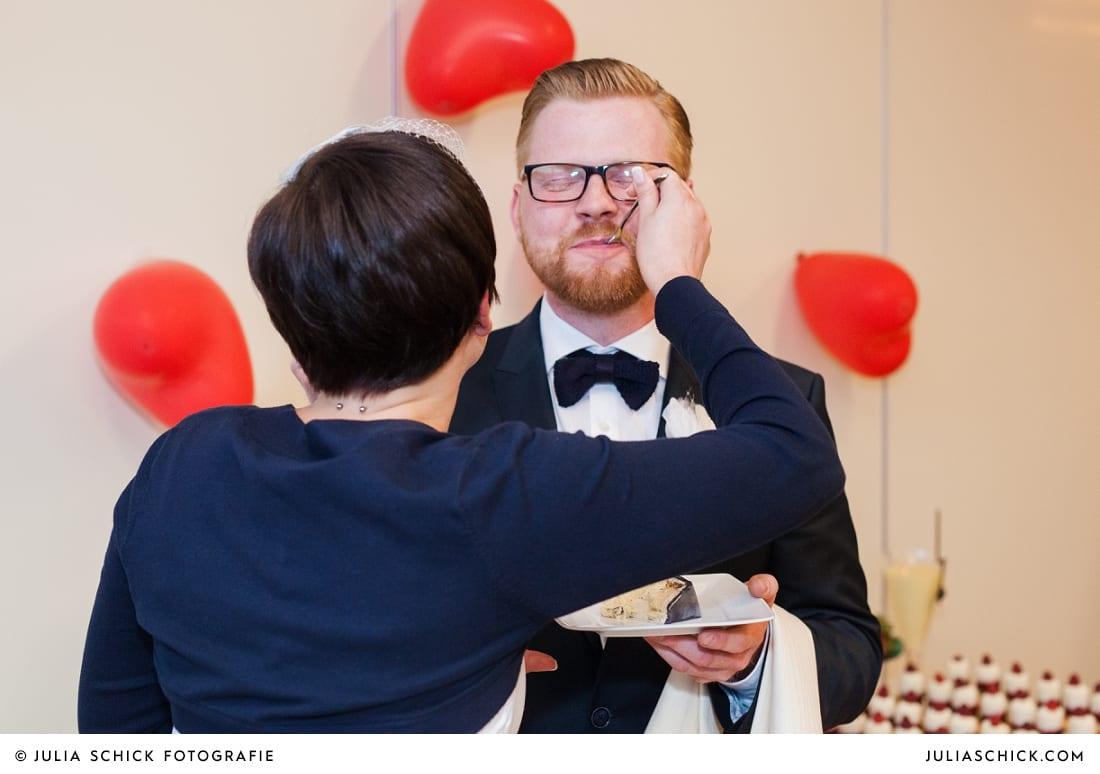 Braut füttert Bräutigam mit Torte