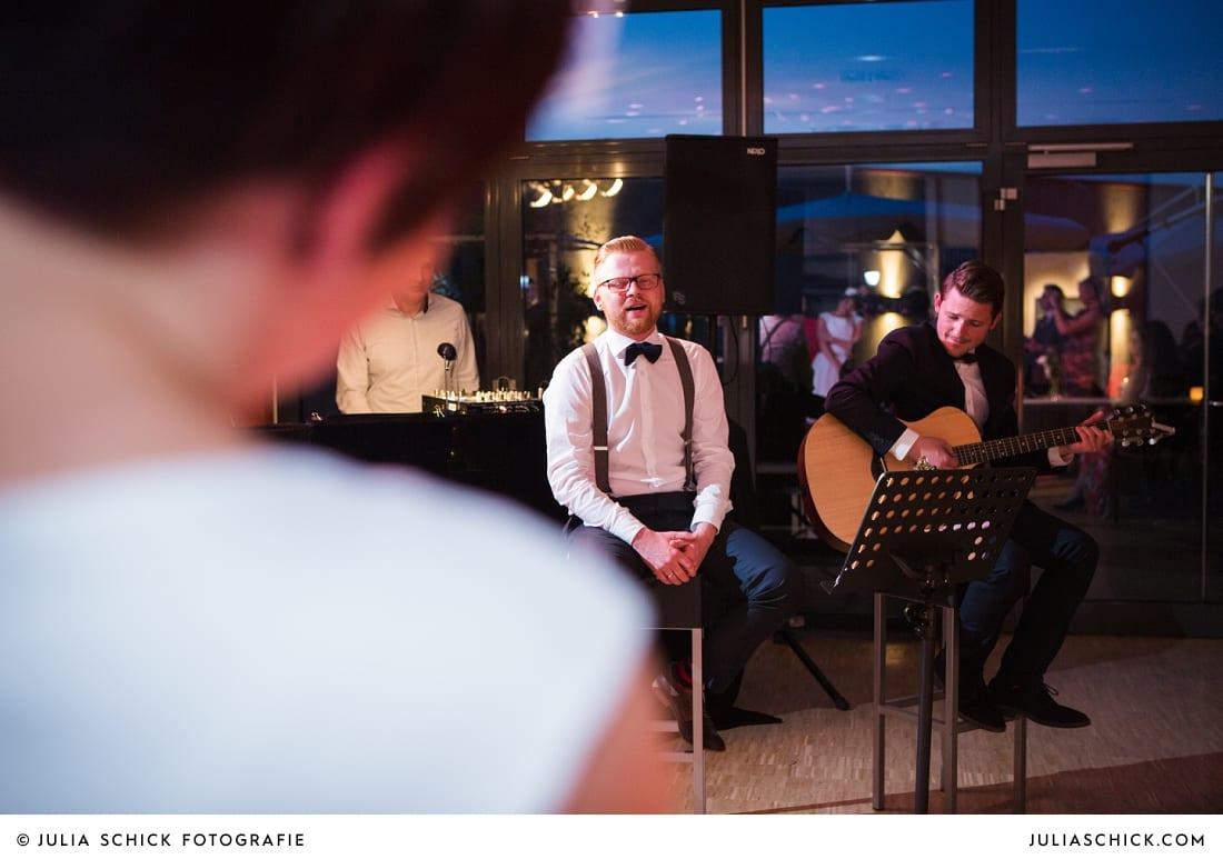 Bräutigam und Trauzeuge singen für Braut bei Hochzeit