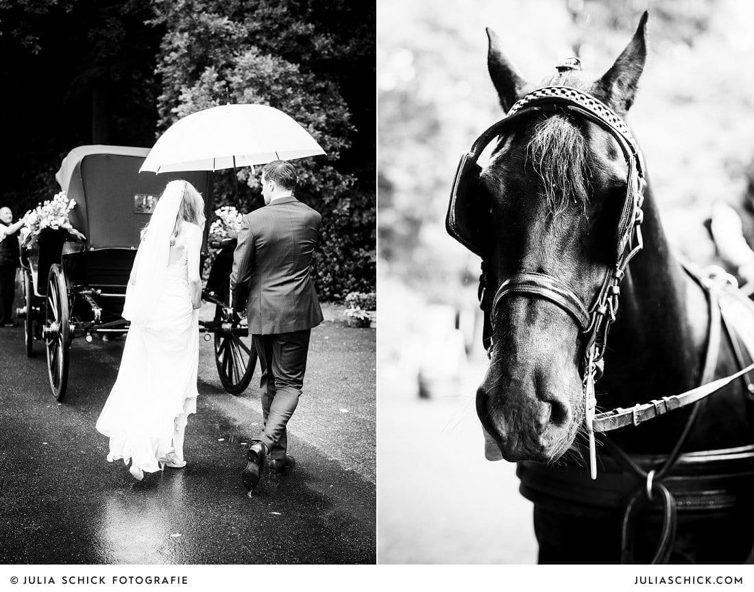 Brautpaar mit Regenschirm auf dem Weg zur Hochzeitskutsche mit Frisenpferden