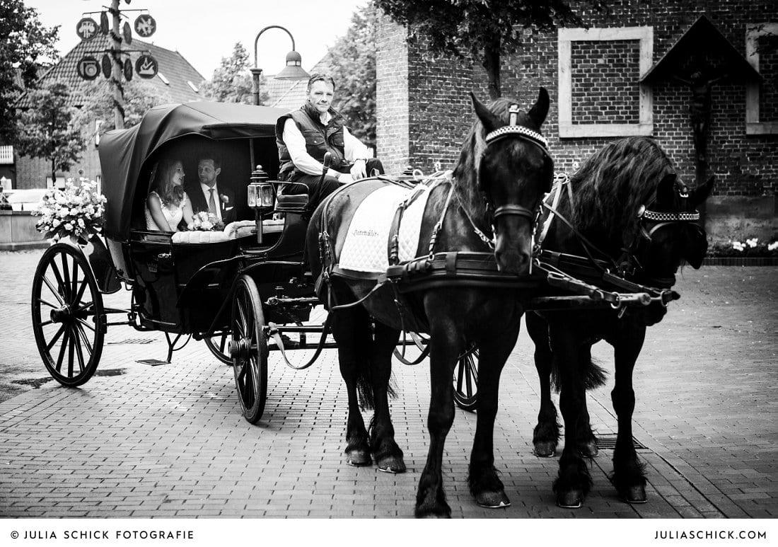 Hochzeitspaar in Hochzeitskutsche mit Friesen