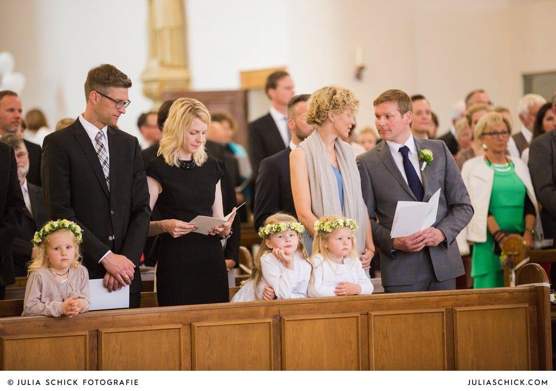 Hochzeitsgäste und Blumenkinder mit Blumenkränzen in der Kirche St. Mariä Himmelfahrt in Ahaus Alstätte