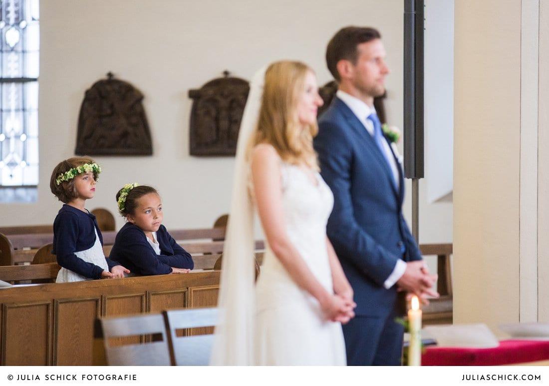 Gelangweilte Blumenkinder im Hintergrund hinter Brautpaar bei kirchlicher Hochzeit in der in der Kirche St. Mariä Himmelfahrt in Ahaus Alstätte
