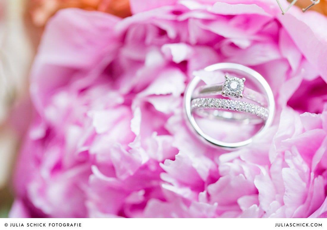 Eheringe und Verlobungsring auf rosa Pfingstrose