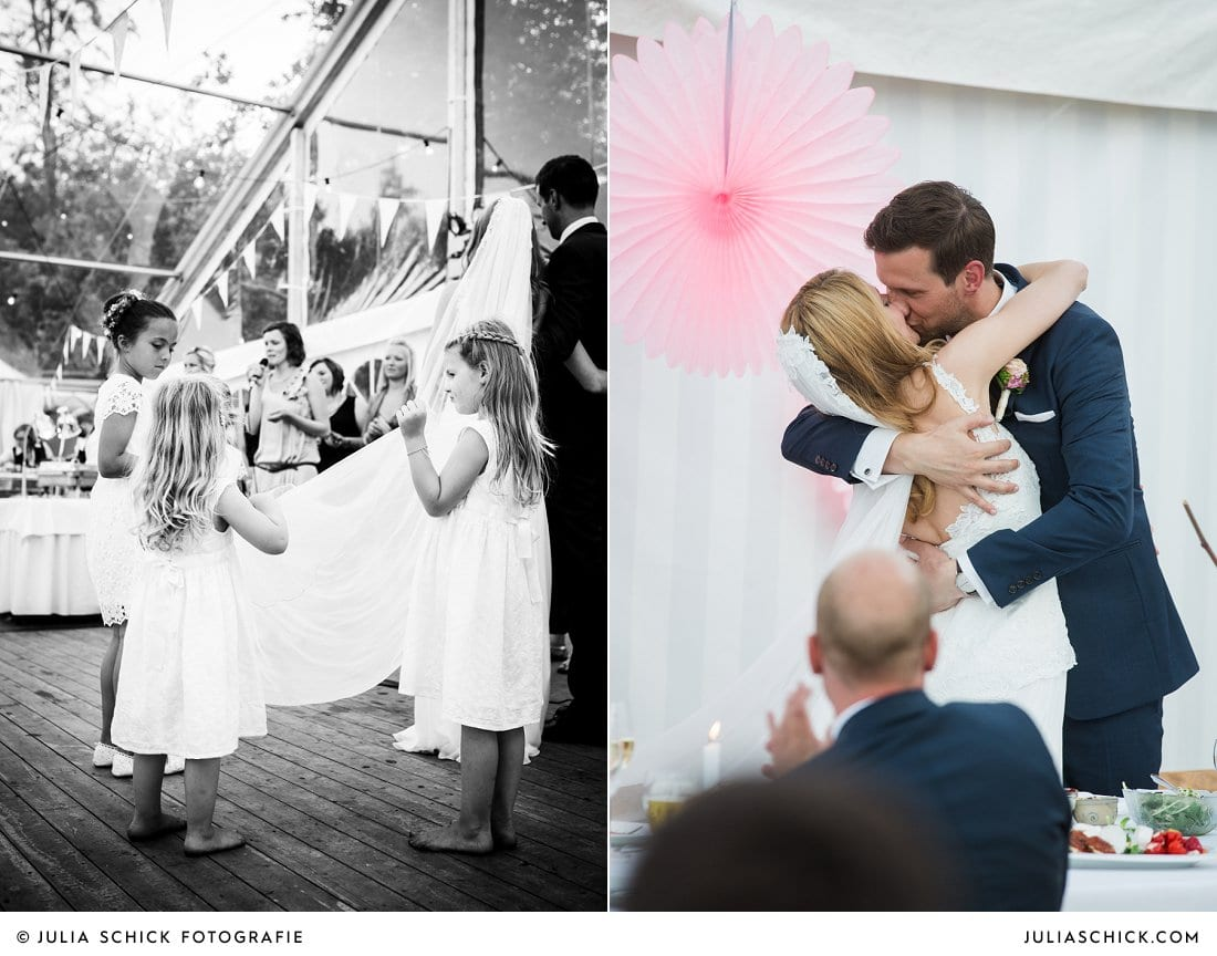Blumenkinder und küssendes Brautpaar vor Hochzeitsdekoration