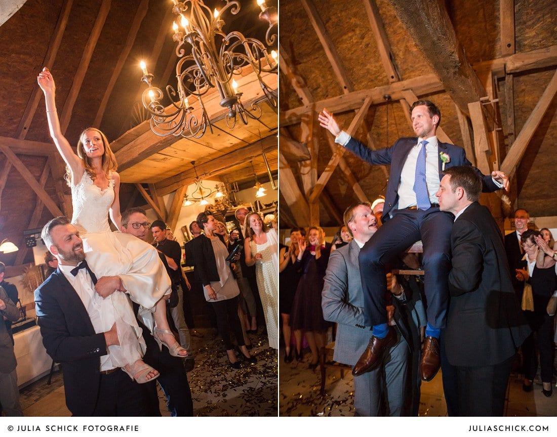 Brautpaar wird auf den Schultern von Gästen getragen bei Hochzeitsfeier in der Festscheune des Gasthaus Haarmühle