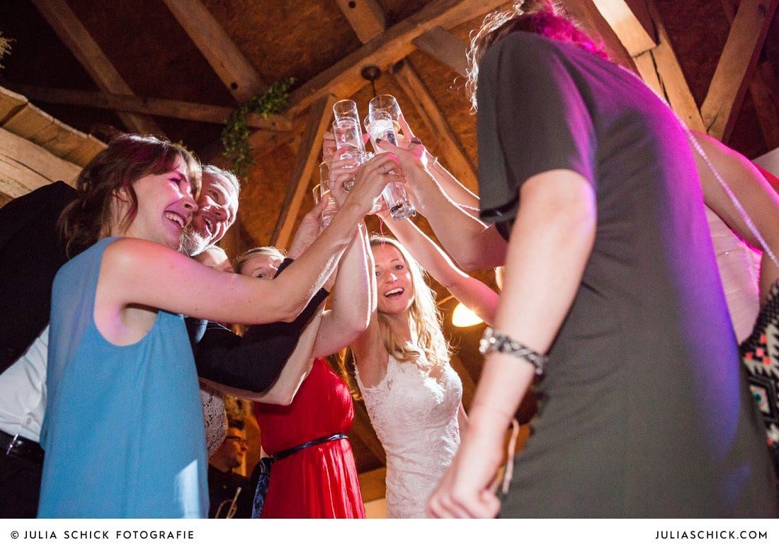 Braut stößt an mit Gästen bei Hochzeitsfeier in der Festscheune des Gasthaus Haarmühle in Ahaus Alstätte