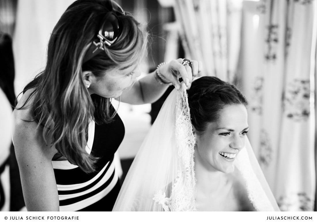 Stylistin steckt Braut den Schleier bei Getting Ready im Fischerhaus des Hof zur Linde in Münster Handorf