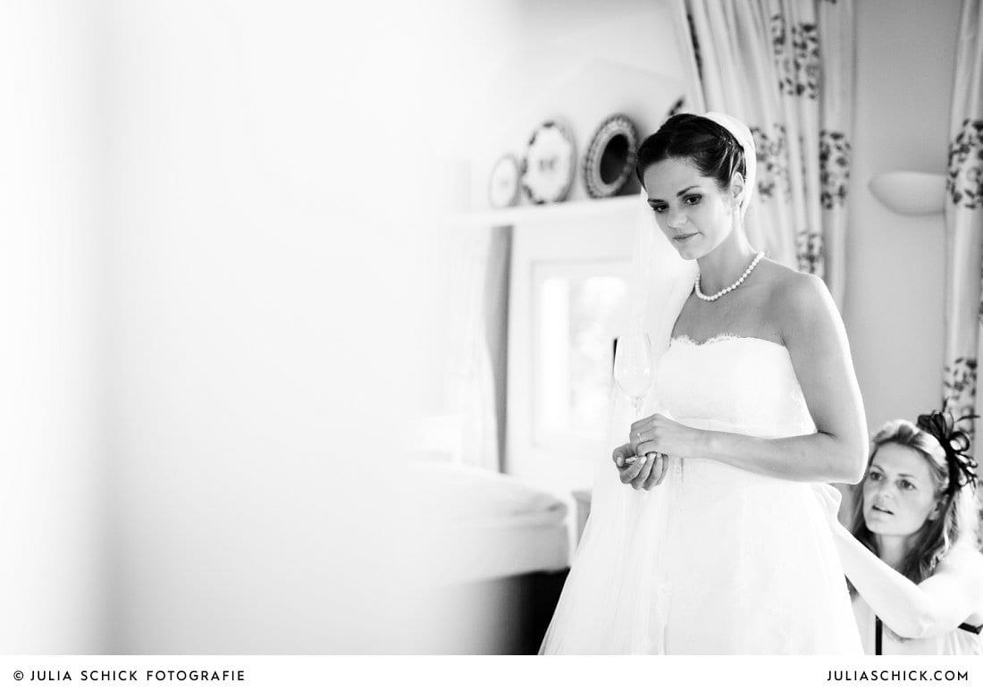 Trauzeugin hilft der Braut ins Hochzeitskleid bei Getting Ready im Fischerhaus des Hof zur Linde in Münster Handorf
