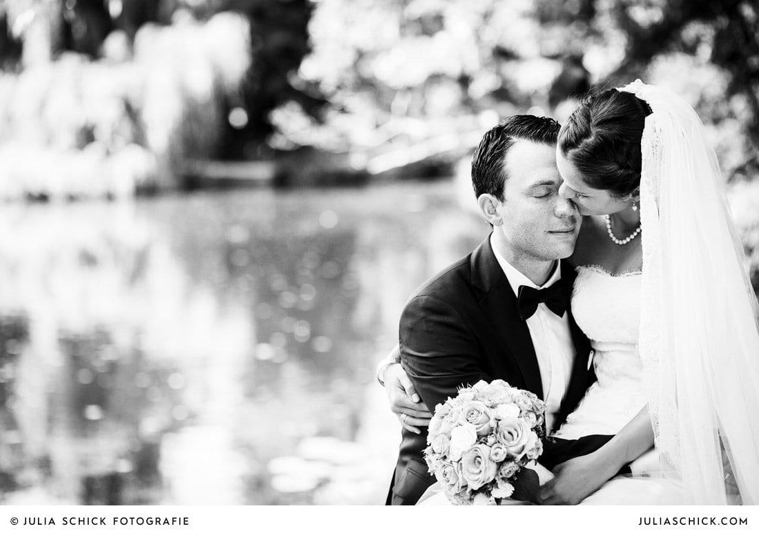 Schwarz-weiß Hochzeitsfoto von schmusendem Brautpaar am Ufer der Werse auf dem Hof zur Linde