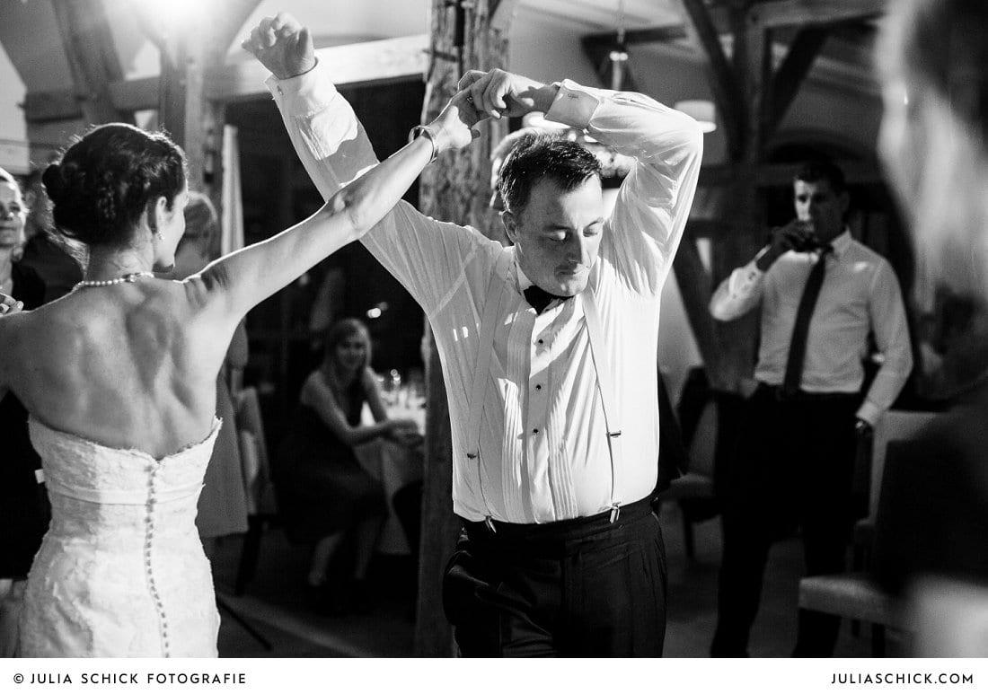 Braut tanzt auf Hochzeit mit Gast im Hof zur Linde