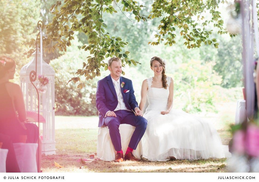 Sitzendes Brautpaar bei freier Trauung an der Schlossruine Hertefeld in Weeze