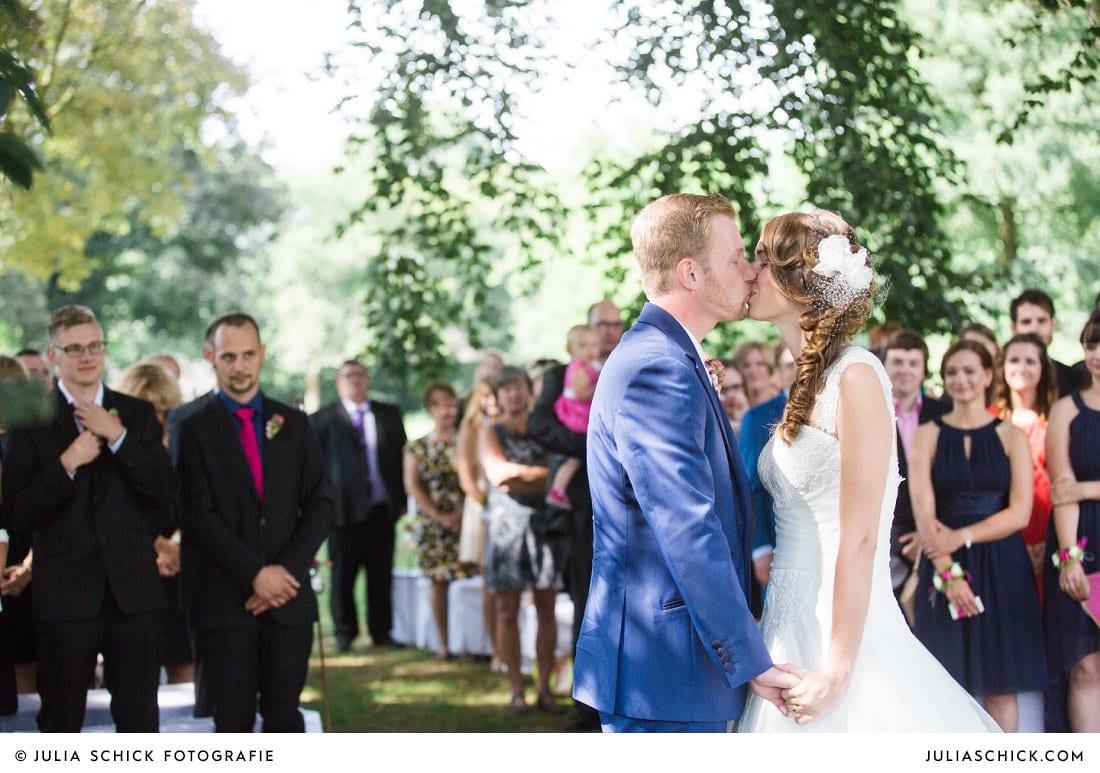 Küssendes Brautpaar währen freier Trauung an der Schlossruine Hertefeld in Weeze