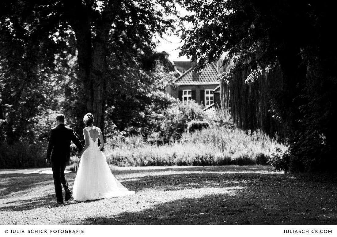 Brautpaar geht zum Sektempfang nach der freien Trauung an der Schlossruine Hertefeld in Weeze
