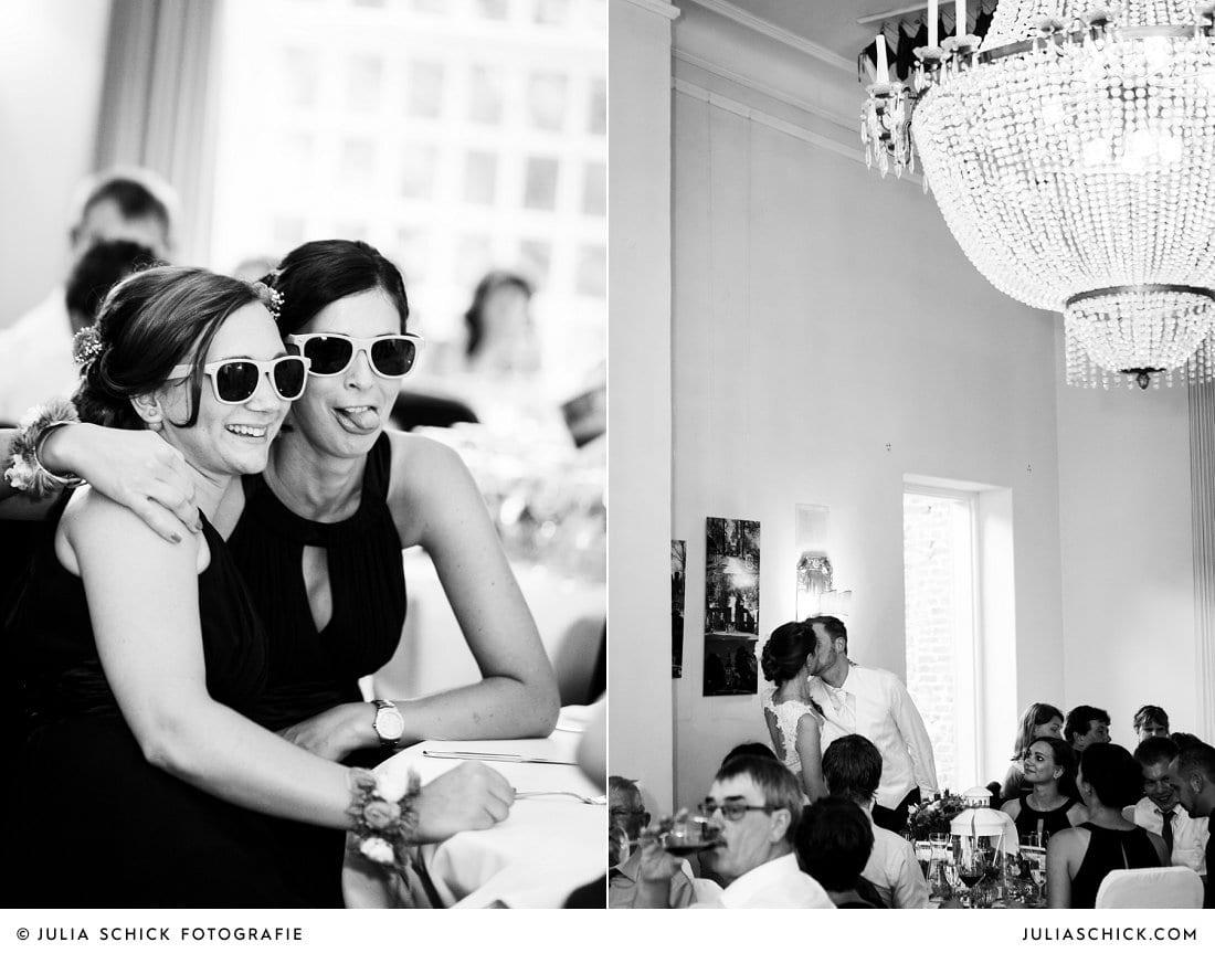 Gäste und küssendes Brautpaar bei Hochzeitsessen im Kaminsaal der Schlossruine Hertefeld in Weeze