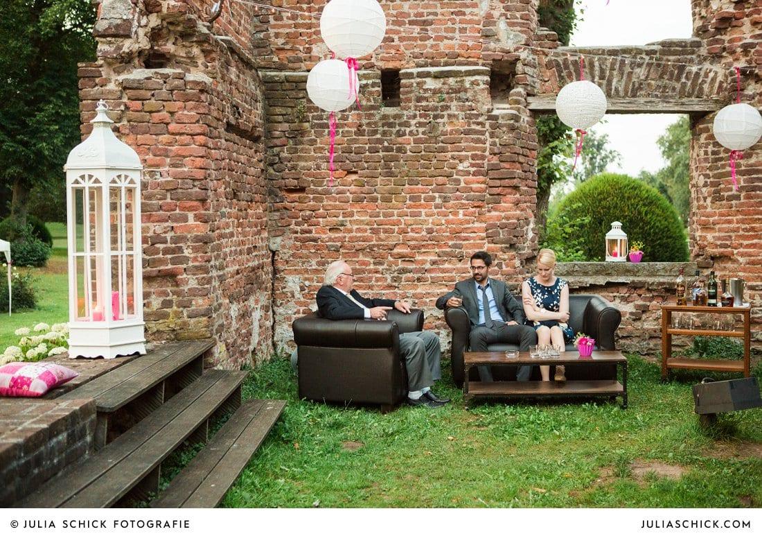 Gäste sitzen an der Whiskeybar bei Hochzeitsfeier in der Schlossruine Hertefeld bei Weeze