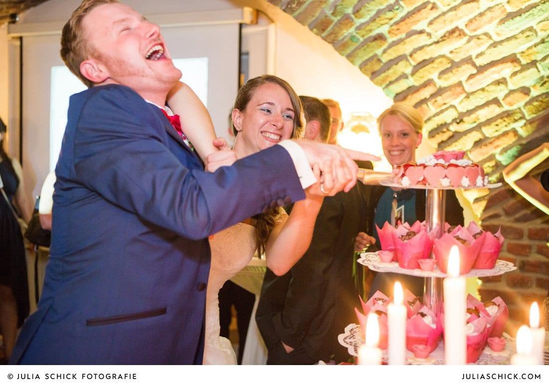 Brautpaar beim Anschneiden der Hochzeitstorte bei Hochzeitsfeier im Kreuzgewölbe der Schlossruine Hertefeld in Weeze