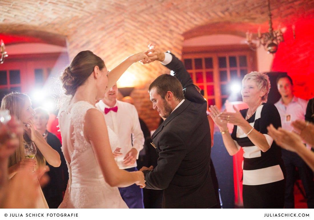 Braut tanzt mit Gast bei Hochzeitsfeier im Kreuzgewölbe der Schlossruine Hertefeld in Weeze