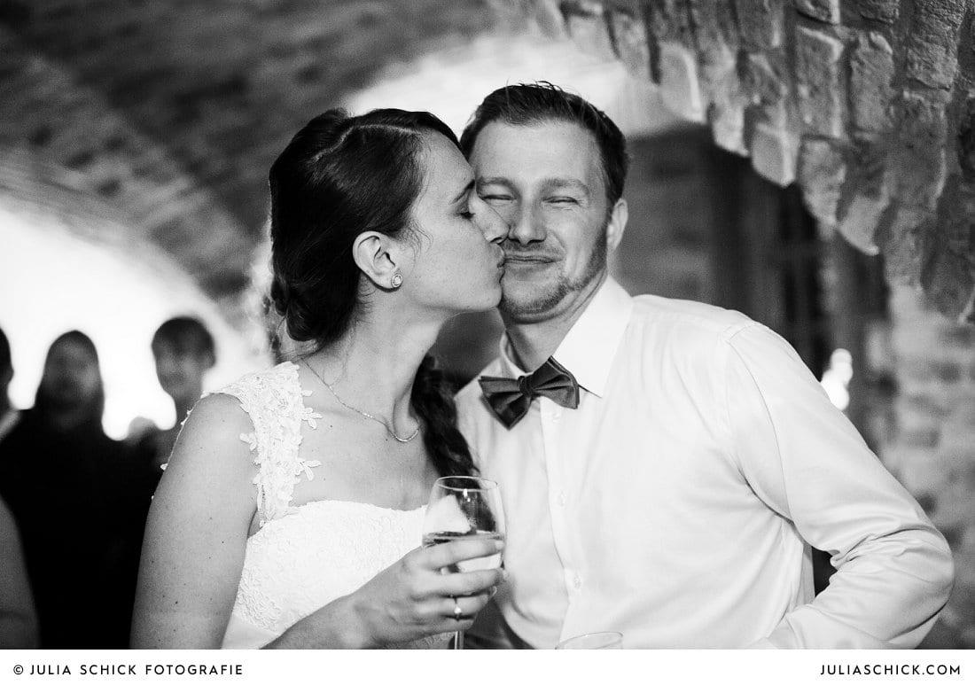 Küssendes Brautpaar bei Hochzeitsfeier im Kreuzgewölbe der Schlossruine Hertefeld in Weeze