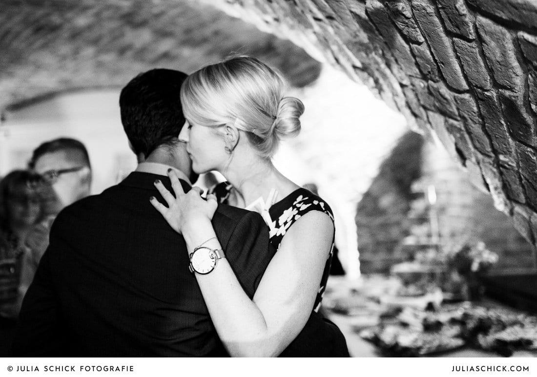 Küssende Gäste bei Hochzeitsfeier im Kreuzgewölbe der Schlossruine Hertefeld in Weeze