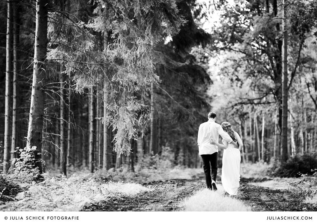Boho Braut in Brautkleid von Grace loves Lace läuft mit Bräutigam durch den Wald in Stadtlohn