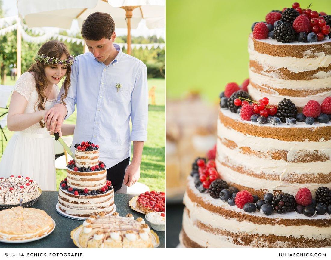 Boho Brautpaar schneidet Naked Cake Hochzeitstorte mit Beerenfrüchten an