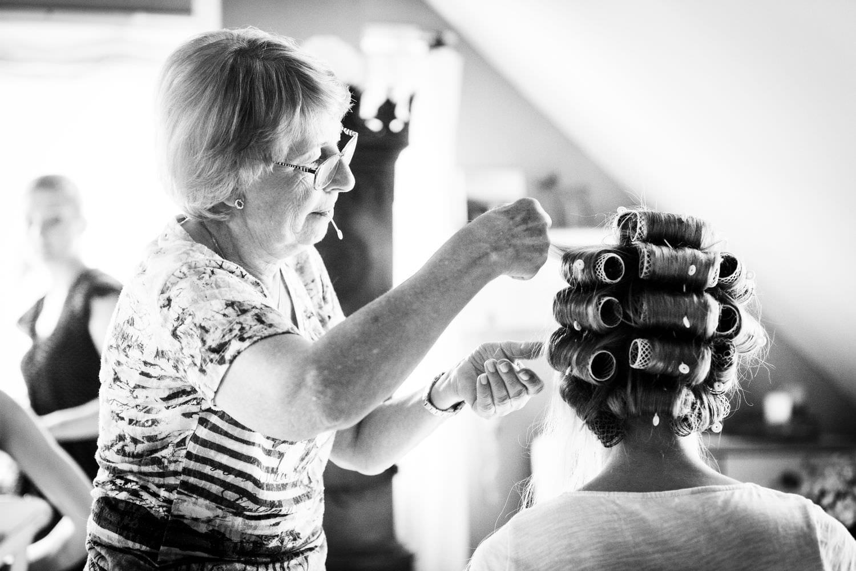 Friseurin macht Braut die Haare als Vorbereitung auf eine Hochzeit auf Schloss Glücksburg