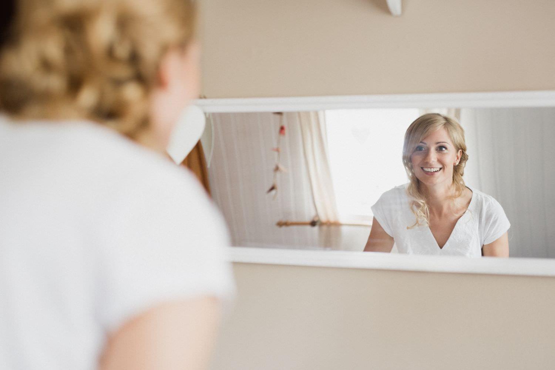 Braut blickt nach Brautstyling begeistert lächelnd in den Spiegel