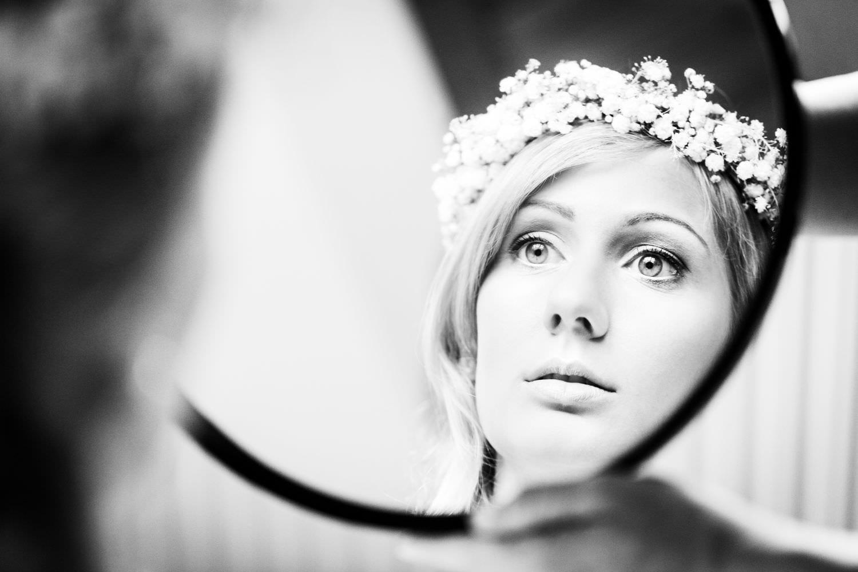 Braut blickt in den Spiegel um zu kontrollieren, ob der Haarkranz gut sitzt