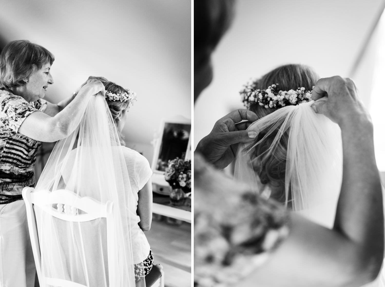 Brautmutter steckt Braut den Schleier ins Haar