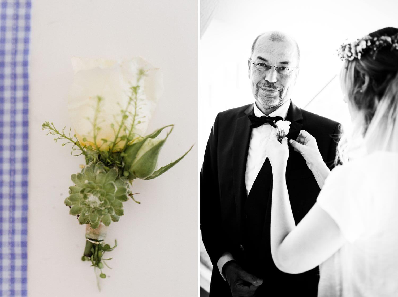 Braut steckt Brautvater im Smoking Blumenanstecker an