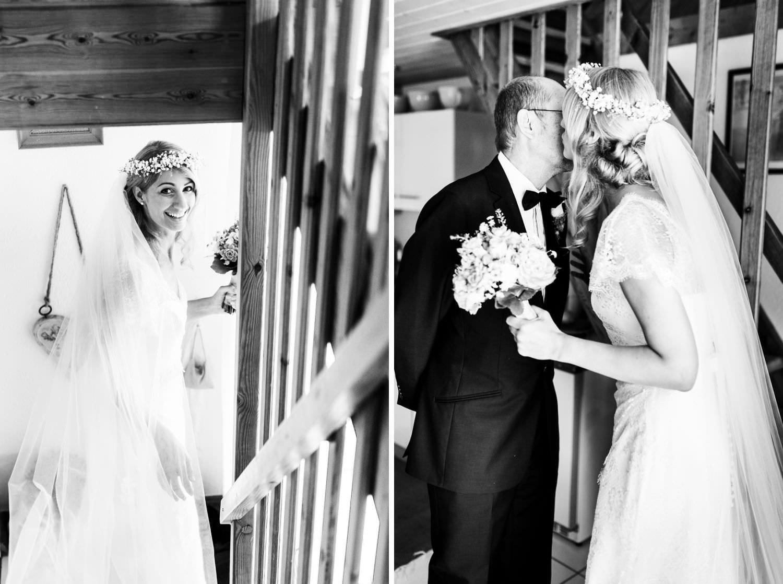 Braut geht Treppe hinunter und küsst Brautvater auf die Wange