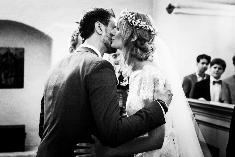 Braut küsst Bräutigam am Altar der Kapelle von Schloss Glücksburg auf die Wange