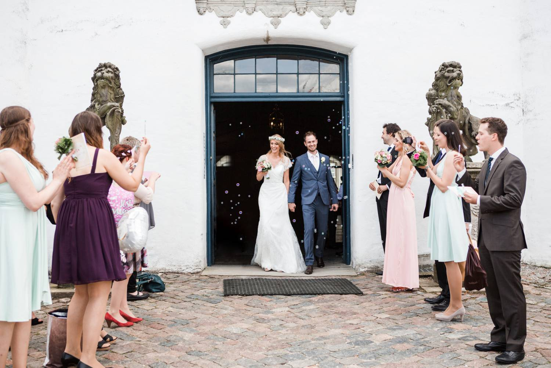 Brautpaar zieht nach kirchlicher Trauung aus Schloss Glücksburga su