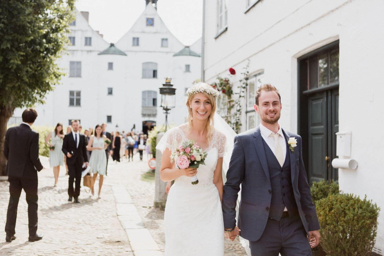Brautpaar geht über den Innenhof von Schloss Glücksburg Richtung Orangerie