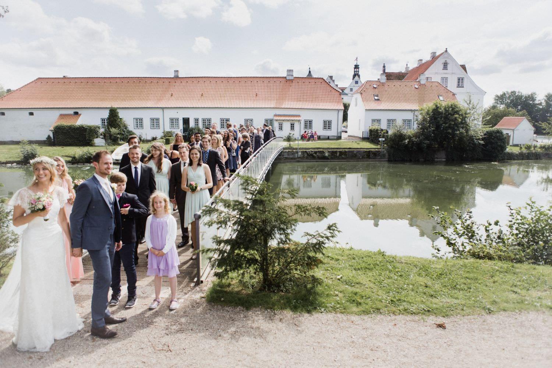 Brautpaar und Hochzeitsgäste gehen mit Hochzeitsgästen über Brücke am Schloss Glücksburg zur Orangerie
