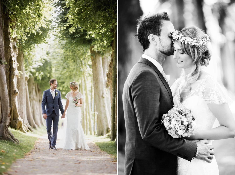Braut und Bräutigam gehen Allee im Garten von Schloss Glücksburg entlang