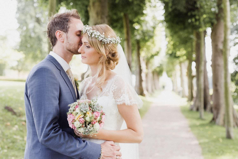 Braut und Bräutigam küssen sich auf Allee im Garten von Schloss Glücksburg entlang