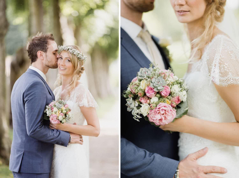 Bräutigam küsst Braut im Garten von Schloss Glücksburg auf die Wange