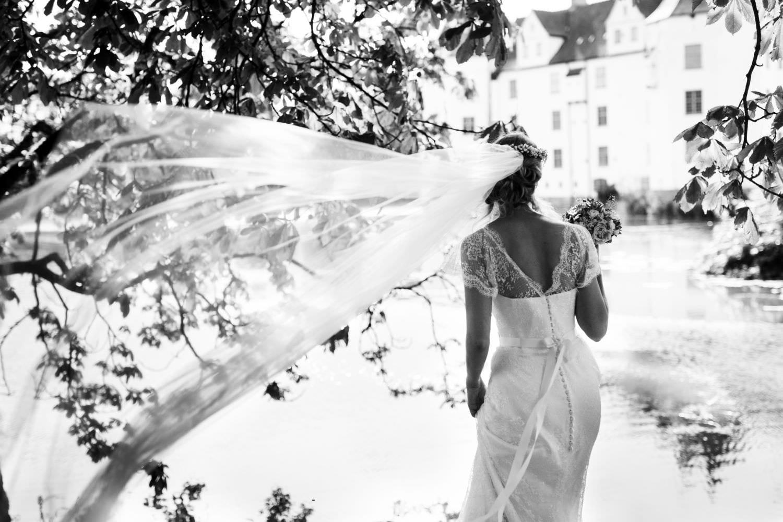 Braut mit wehendem Schleier vor Schloss Glücksburg