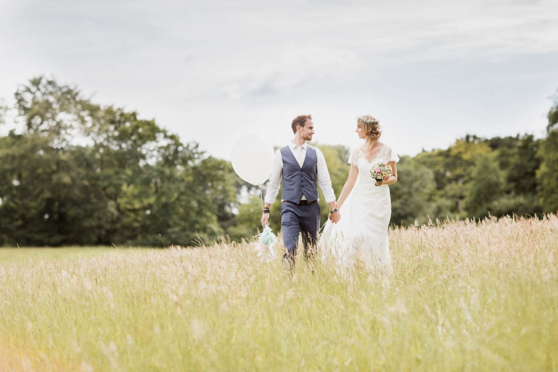 Boho-Brautpaar auf wilder Wiese in der Nähe von Schloss Glücksburg