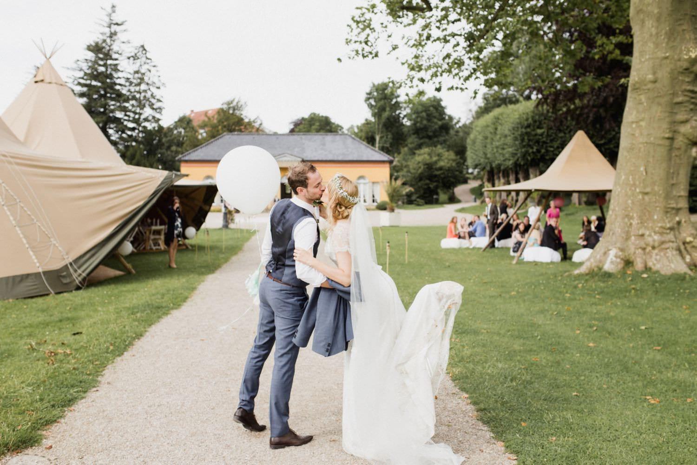 Brautpaar küsst sich auf dem Weg zur Hochzeitsfeier in der Orangerie von Schloss Glücksburg