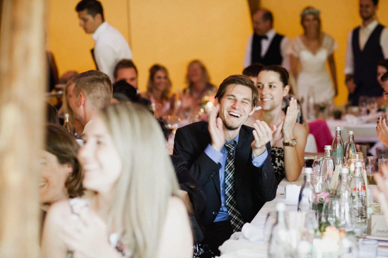 Lachender Hochzeitsgast bei Hochzeitsrede