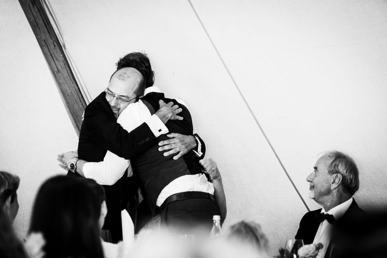 Vater der Braut umarmt den Bräutigam nach seiner Rede