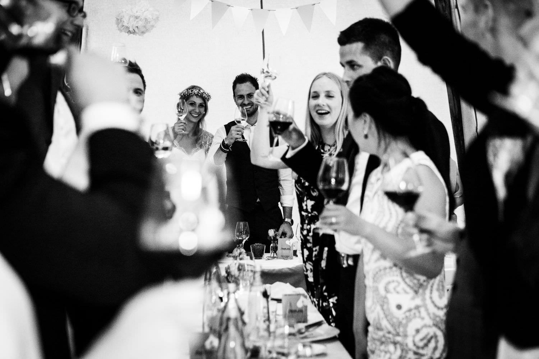 Gäste prosten nach Toast dem Brautpaar zu bei einer deutsch-dänischen Boho-Hochzeit auf Schloss Glücksburg im Tipi.