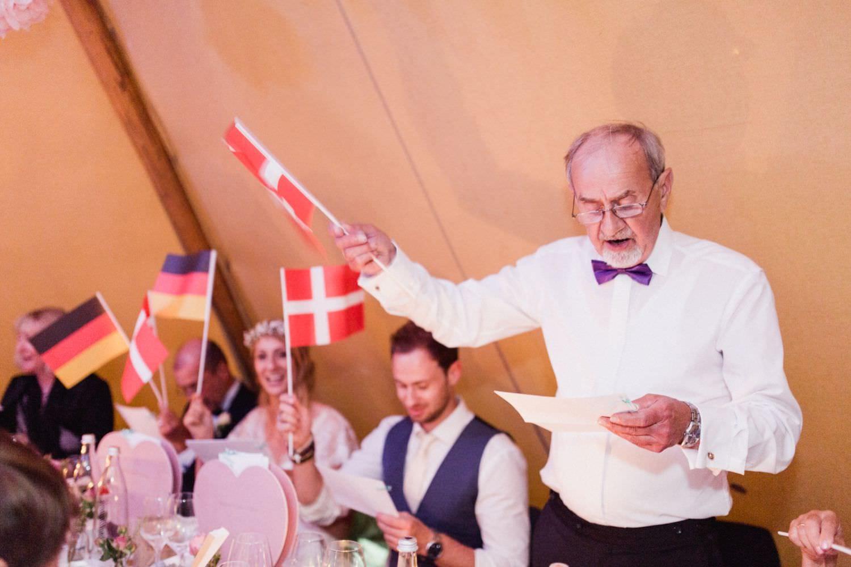 Bräutigamvater schwenkt bei Tipi-Hochzeit die dänische Fahne während er ein selbtgedichtetes Lied singt