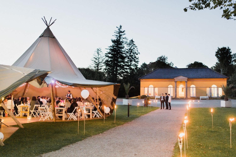 Hochzeitsgesellschaft sitzt in Tipi auf der Wiese vor der Orangerie von Schloss Glücksburg und hört der Rede des Bräutigams zu.