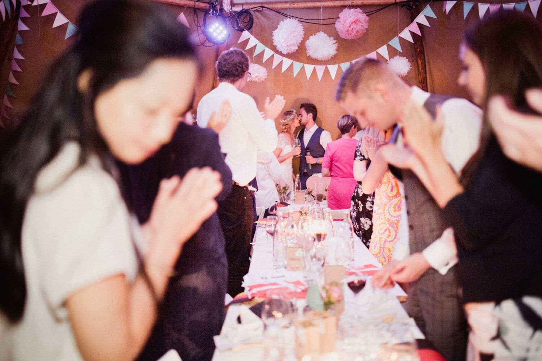 Gäste porsten sich küssenden Brautpaar bei Hochzeit im Tipi zu.