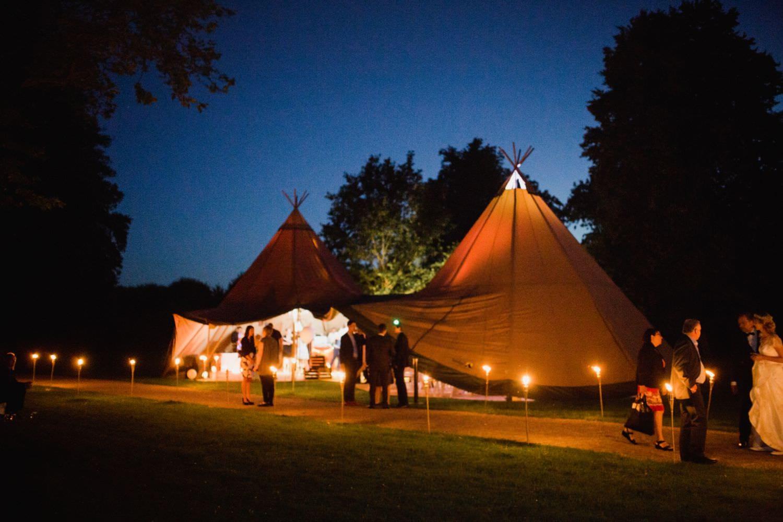 Erleuchtetes Tipi zur blauen Stunde bei Boho-Hochzeit auf der Wiese vor der Orangerie des Schloss Glücksburg