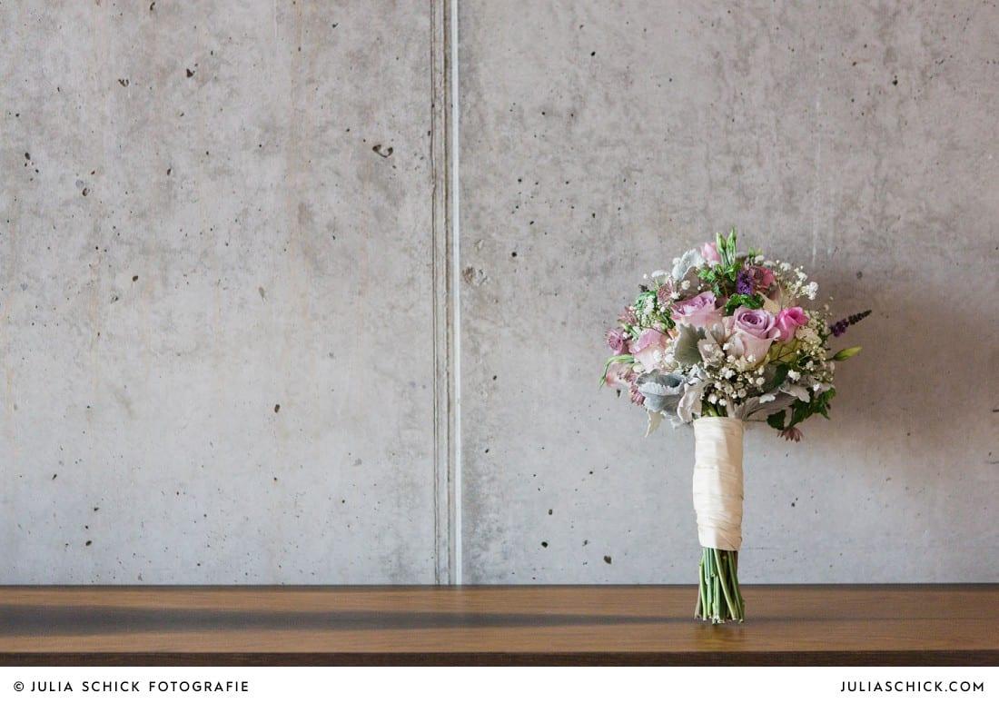 Brautstrauß von die Floristen in Münster vor Betonwand im Factory Hotel