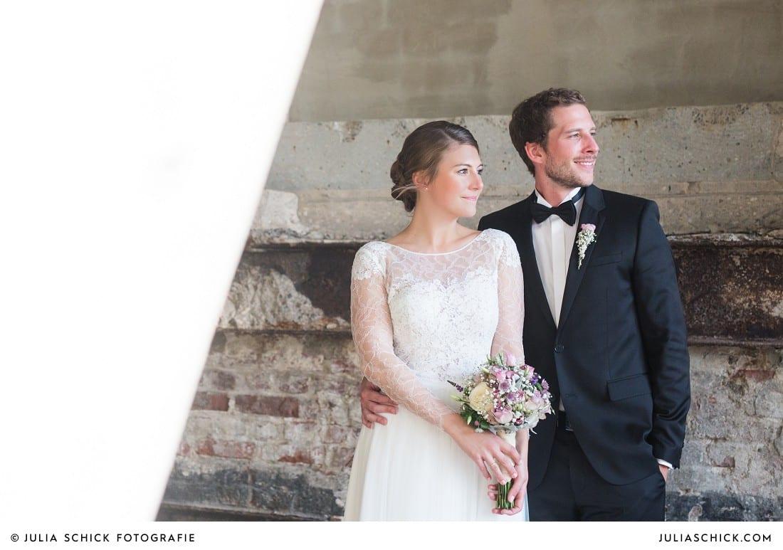 Brautpaar in Hochzeitskleid von Anna Kara und Smoking vor Ziegelwand mit Stahlträgern am Factory Hotel in Münster